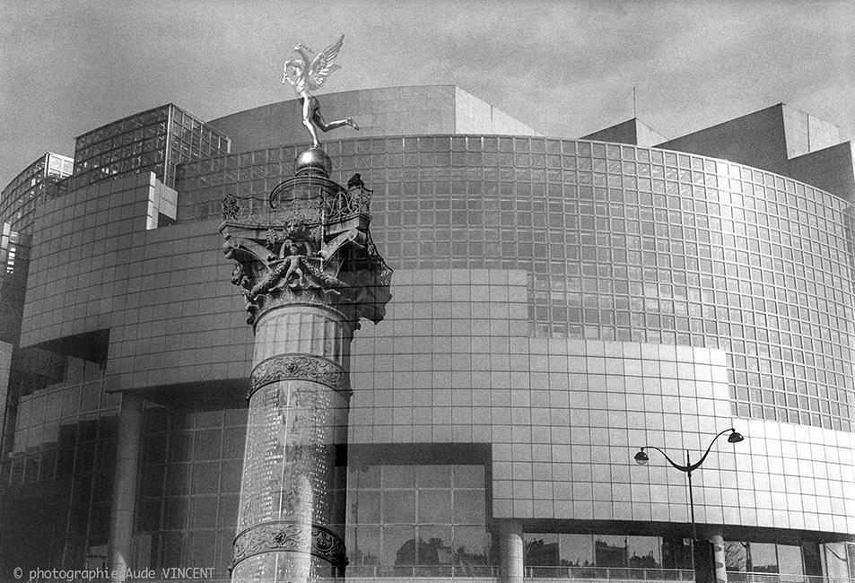 """Photographie d'auteur argentique noir et blanc extraite de la série """"Paris, Paris, Paris, la ville lumière sans cliché"""" de la photographe française et parisienne Aude VINCENT.   L'Opéra Bastille, place de la Bastille, le Génie de la Bastille et la c"""