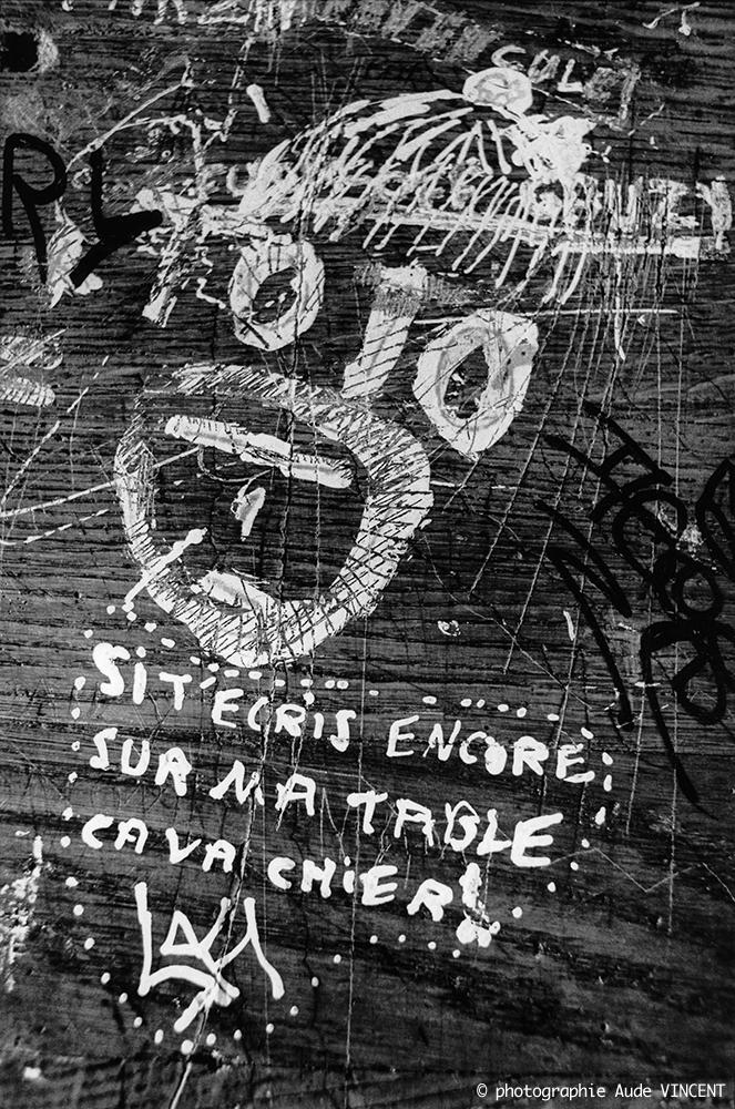 """photographie en noir & blanc extraite de la série """"Les pupîtres de la nation"""" : les graffitis laissés sur les tables d'école par les lycéens."""