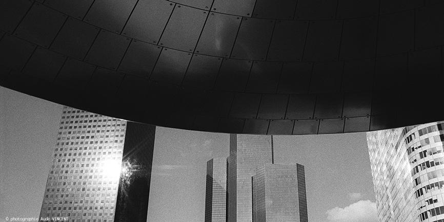 """Photographie d'auteur argentique noir et blanc extraite de la série """"Paris, Paris, Paris, la ville lumière sans cliché"""" de la photographe française et parisienne Aude VINCENT.  Tours de La Défense, quartier d'affaires situé dans la Métropole du Gra"""