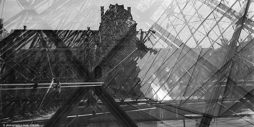 """Photographie d'auteur argentique noir et blanc extraite de la série """"Paris, Paris, Paris, la ville lumière sans cliché"""" de la photographe française et parisienne Aude VINCENT. Le Louvre et la Pyramide du Louvre abritent le Musée du Louvre au centre d"""